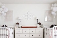 a gender neutral shared nursery with white furniture, white paper lamps, a mother of pearl chandelier and striped bedding