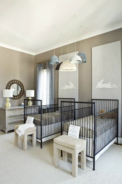 a gender neutral shared nursery with neutral furniture, black cribs, printed bedding and touches of grey and blue, with crochet lamps