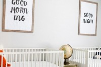 a gender neutral shared nursery with a printed rug, neutral beds, graphic artworks and a gold chest with a globe on it