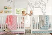 a neutral shared nursery with a fun giraffe on the wall, bookshelves and pink and blue linens to differentiate the boy and the girl zone
