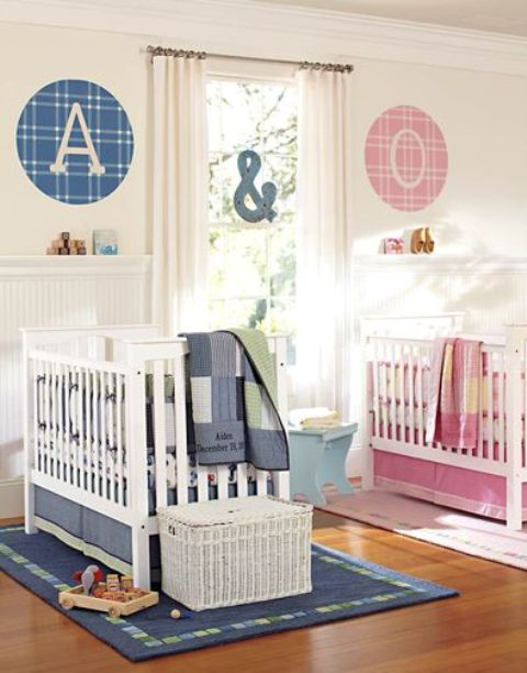 a neutral shared nursery with white paneling and furniture, with blue and pink linens and monograms to highlight each place