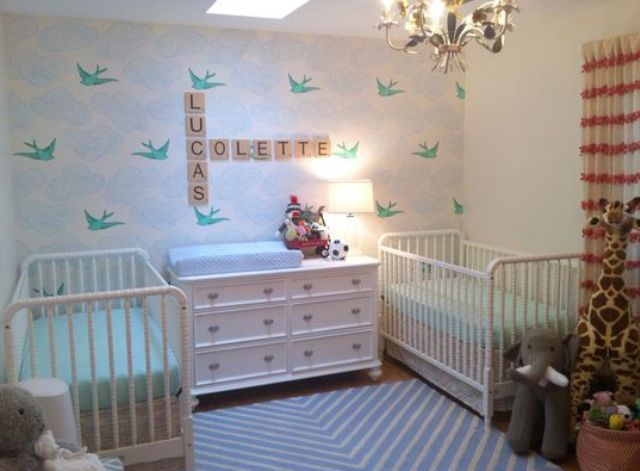a neutral and pastel shared nursery with a skylight, a birdie wall, white furniture and pastel bedding and lots of toys