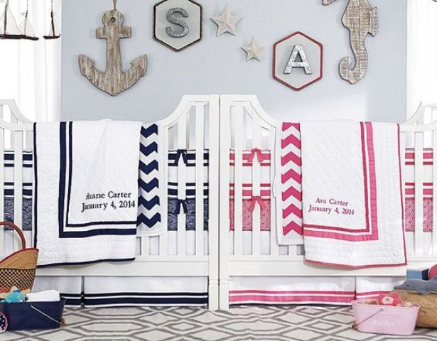 a nautical shared nursery with light blue walls, white furniture, a seaside gallery wall and navy and pink and white bedding