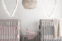 a peaceful neutral shared nursery with grey furniture, light hearts, a crochet chandelier and pink and blue bedding