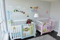 a pastel shared nursery with grey walls, white furniture, colorful images and letters on the wall and pink and blue bedding