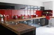 a bold red and black contemporary kitchen with a glossy backsplash and butcherblock countertops plus stainless teel appliances is very bold and cool