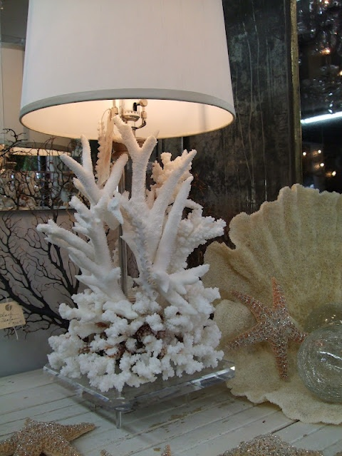 a seaside table lamp with corals at the base and a neutral lampshade is a lovely decoration for a coastal interior