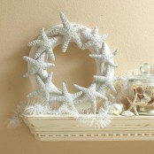 a beach mantel with a starfish wreath, a jar with seashells and starfish plus a feather garland