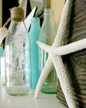 sheer and blue bottles with rope and a starfish on the mantel to make it feel beach-like