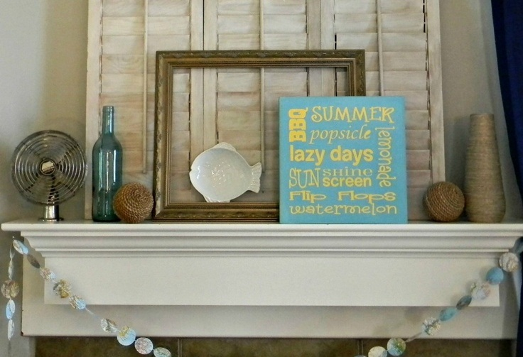 a seashell garland, rope balls, artworks and a blue and yellow beach sign for a simple and bright beach mantel