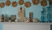 a beach mantel with seashells of various shades, artworks and blue candles in blue candleholders