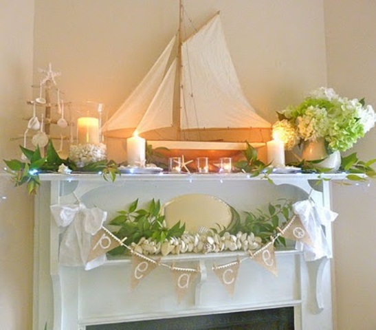 a refined beach mantel with candles, green and white hydrangeas, a large boat, a burlap garland and greenery and white flowers