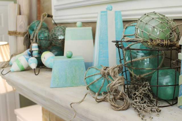 a beach mantel with blue glass floats, colorful striped floats and creative striped candles in pyramide shapes