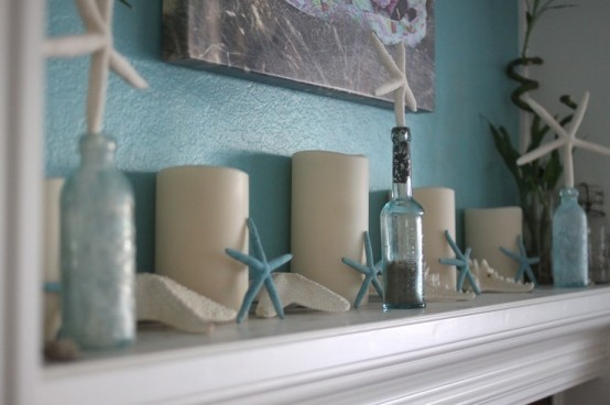 a blue and neutral beach mantel with blue starfish, candles, bottles with starfish stoppers