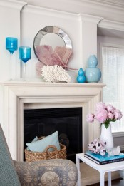 a beach mantel with blue glasses and vases, corals and starfish and a large geometric mirror