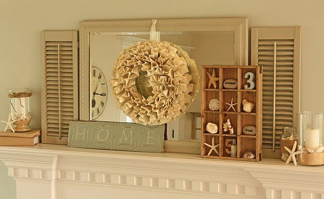 a neutral beach mantel with a mirror, a burlap wreath, a box with seashells, starfish and candleholders with starfish