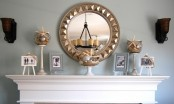 jars with beach sand, seashells and starfish, net and some photos on stands make the mantel feel beach-like