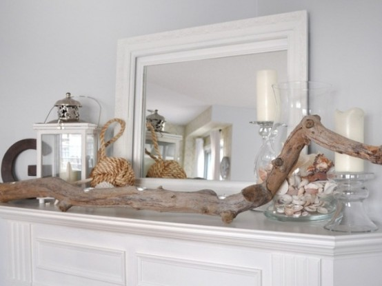 a beach mantel with a driftwood piece, a jar with seashells, candles and candle lanterns
