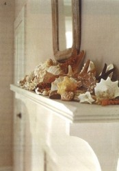 a mantel with lots of seashells and a mirror over it is a simple way to bring a beachy feel to your space