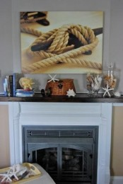 a simple beach mantel with starfish and seashells, large jars with seashells and starfish and a rope artwork over it