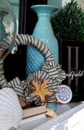 seashells, starfish, a fabric wreath, a blue vase, a crochet art for a simple and relaxed beach mantel