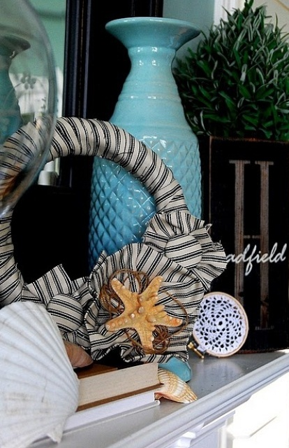 seashells, starfish, a fabric wreath, a blue vase, a crochet art for a simple and relaxed beach mantel