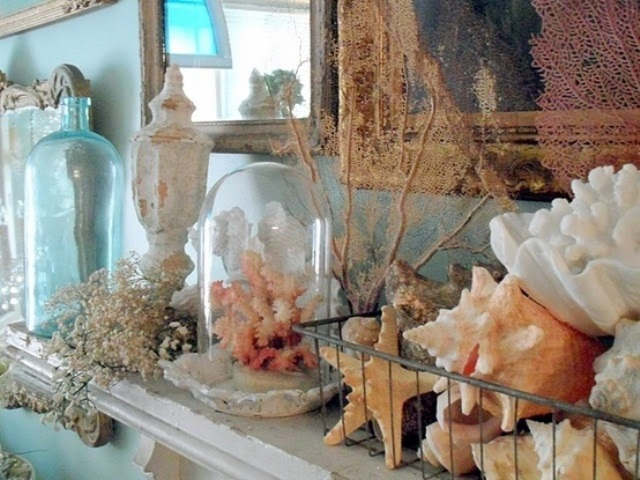 a cloche with a pink coral, more corals, starfish and seashells, vintage bottles and jars