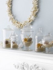 a stylish beach mantel with large clear jars with various seashells and beach sand and a coral wreath over the mantel