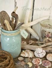a mantel with seashells, starfish, jars with driftwood and seashells, rope looks beach-like and very enjoyable
