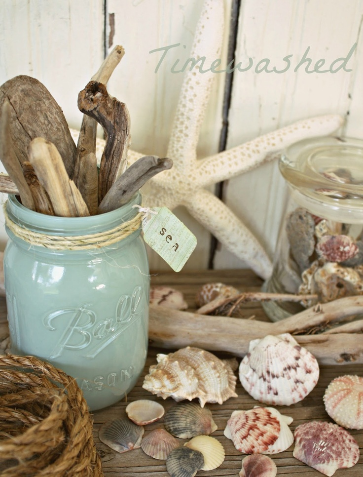 a mantel with seashells, starfish, jars with driftwood and seashells, rope looks beach like and very enjoyable