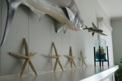 a beach mantel with starfish, a candle in a blue candleholder and some fish over the mantel is very cool