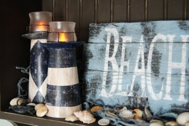 a mantel covered with seashells, beacon candle lanterns and a blue sign that you can DIY