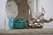 a cool beach mantel with a blue bottle and a blue glass float, a piece of driftwood with seashells attached