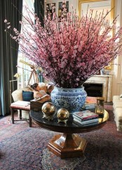 bold pink cherry blossom branches in a blue vase make a bold statement in the space and bring a spring feel to it
