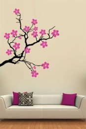 bright cherry blossom decals on the wall over the sofa echoes with the pillows and makes the space bolder