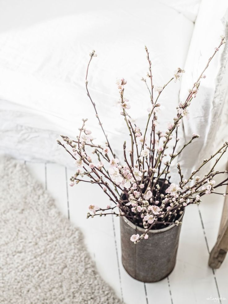 a concrete vase with blooming cherry branches is a great decoration and centerpiece for any space