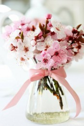 a clear vase with cherry blossom branches and a pink bow is a chic and bold centerpiece