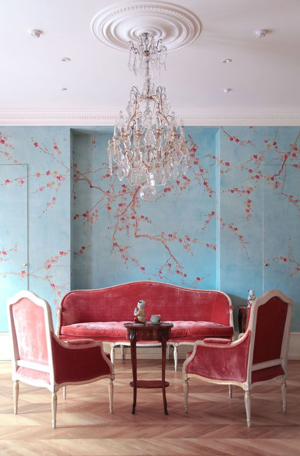 blue walls with cherry blossom decals and matching coral furniture of velvet is a chic idea