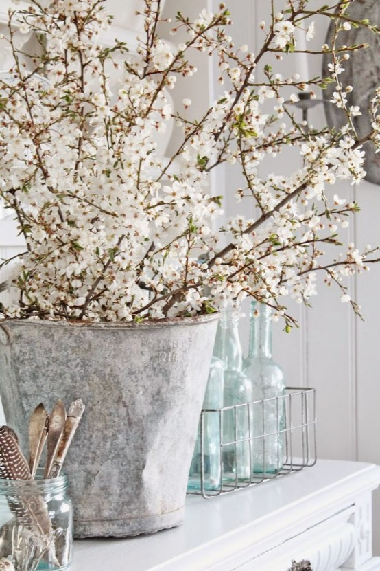 a vintage bucket with lots of blooming branches will bring a cozy rustic feel and a natural touch to the space