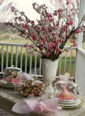 a white vase with pink and blush blooming branches is a beautiful spring or Easter decoration