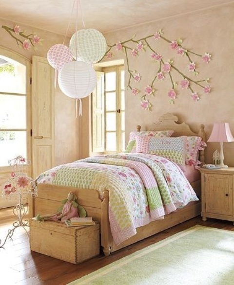 a vintage-inspired kid's bedroom with cherry blossom on the wall that accents the decor of the room