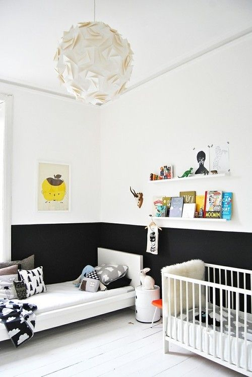 a Nordic black and white nursery with floating shelves, a crib and a bed and a half black wall