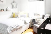 a neutral shared space with touches of grey, yellow and a dark wooden crib plus some prints