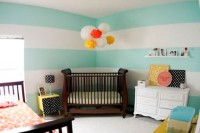 a colorful shared space with striped turquoise walls, dark wooden furniture, colorful touches