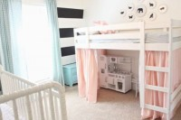 a simple shared space done with a striped wall, two matching beds, pink and blue curtains