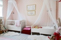 a delightful shared nursery for girls done with pink wallpaper, chic beds, cute toys and fuchsia textiles