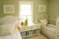 a vintage-inspired green nursery with artworks, elegant beds and a storage unit between them
