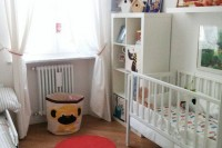 a neutral nursery with red and yellow touches, some bright toys and artworks, a storage basket