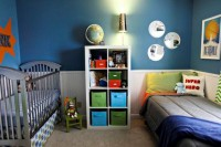 a colorful shared nursery done with a blue wall, colorful textiles and boxes for storage