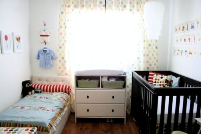 a neutral shared nursery with mismatching beds and colorful and printed bedding